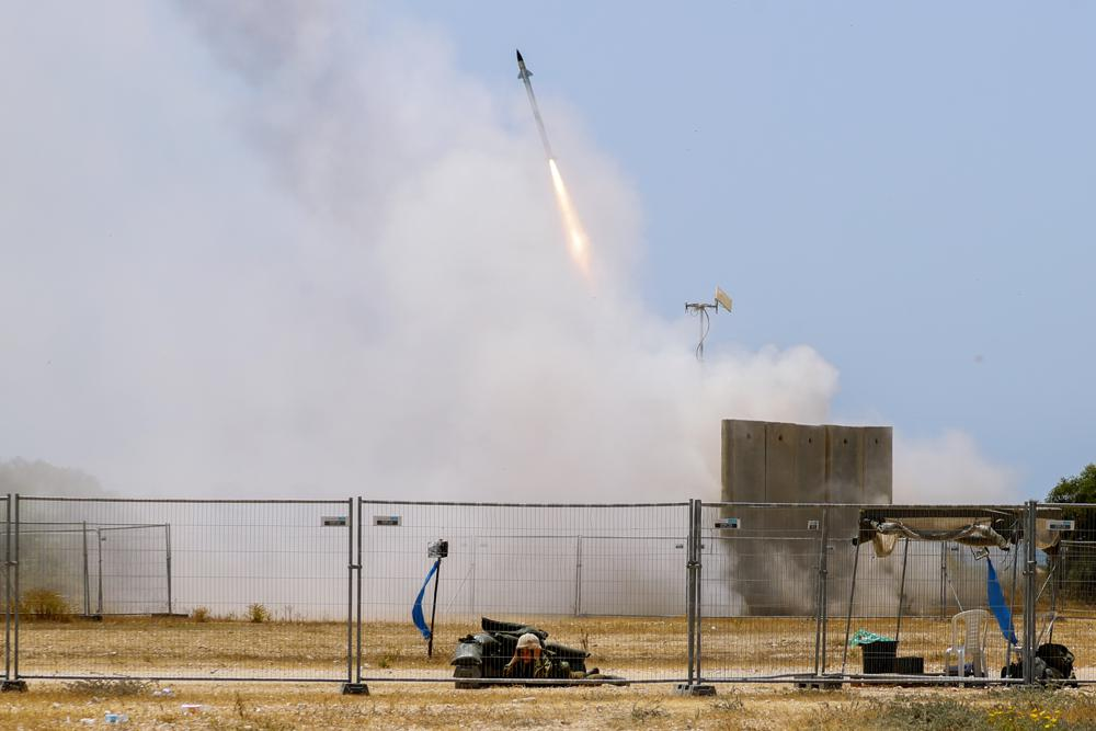 a israeli soldier takes cover as an iron dome air defense system launches to intercept a rocket from the gaza strip