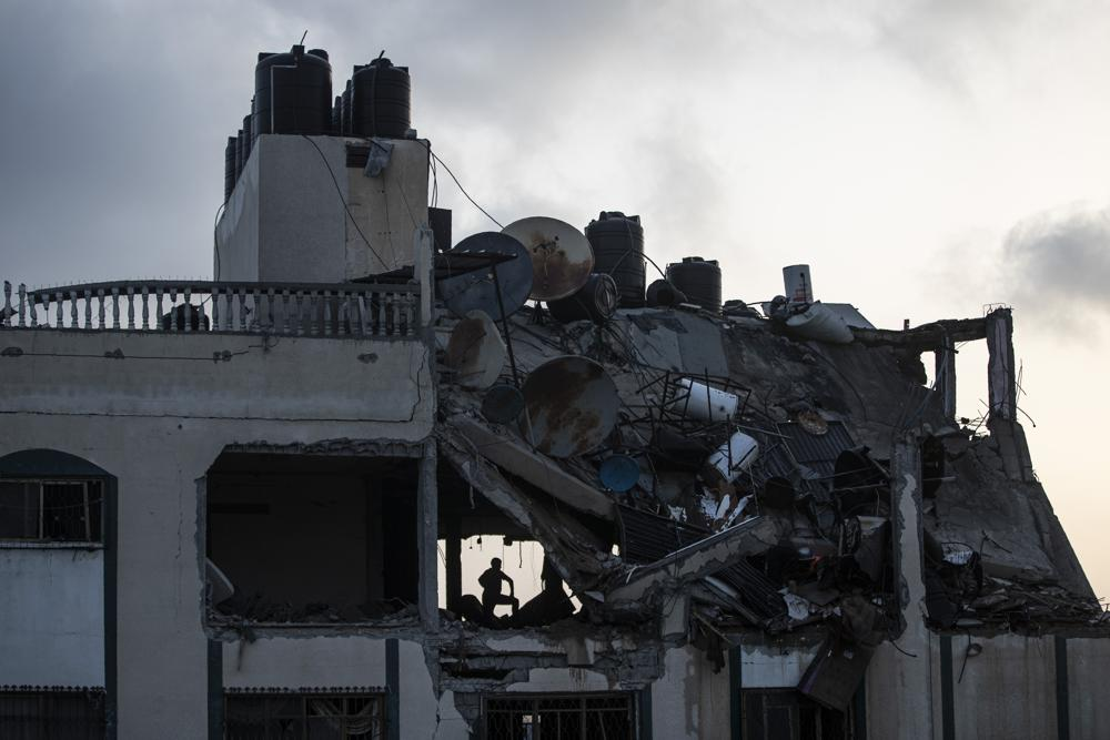 a palestinian searches for survivors under the rubble of a destroyed rooftop of a residential building which was hit by israeli missile strikes