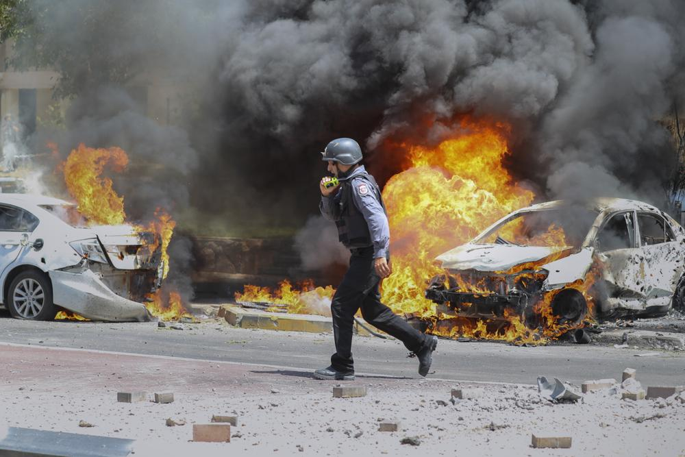 an israeli firefighter walks next to cars hit by a missile fired from gaza strip