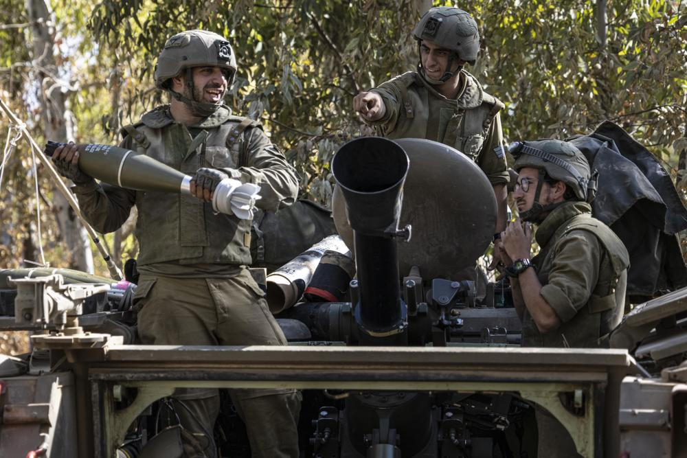 israeli soldiers load ammunition onto an armored personal carrier (apc) at a staging ground near the israeli gaza border