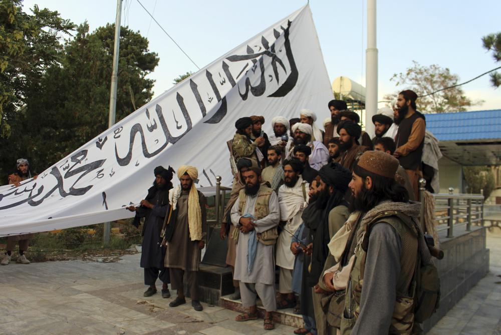 taliban fighters raise their flag at the ghazni provincial governor's house, in ghazni